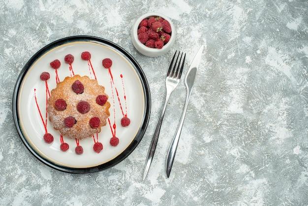 Вид сверху ягодный торт на белой овальной тарелке, малина в миске, вилка и обеденный нож на серой поверхности, свободное пространство