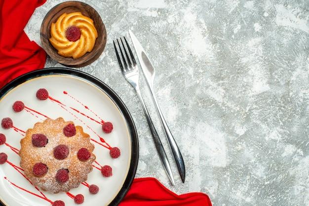 白い楕円形のプレートの上のビューベリーケーキ赤いショールビスケットフォークと灰色の表面のコピースペースのディナーナイフ