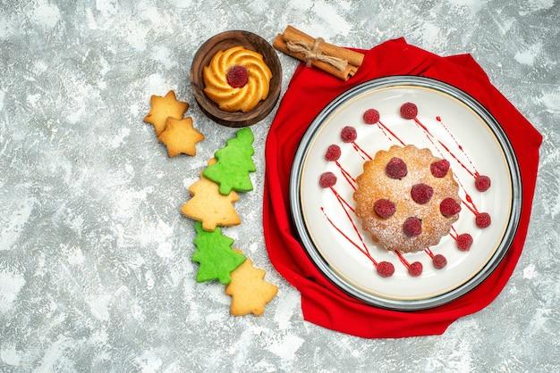 Вид сверху ягодный торт на белой овальной тарелке красный платок палочки корицы печенье на серой поверхности