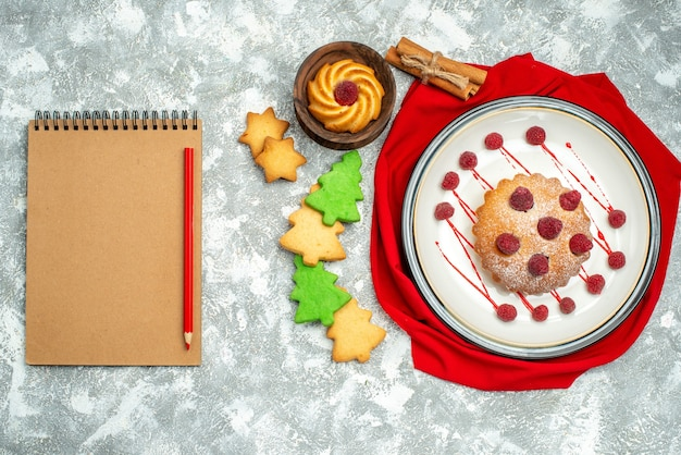 회색 표면에 흰색 타원형 접시 빨간 목도리 노트북 빨간 연필 쿠키에 상위 뷰 베리 케이크