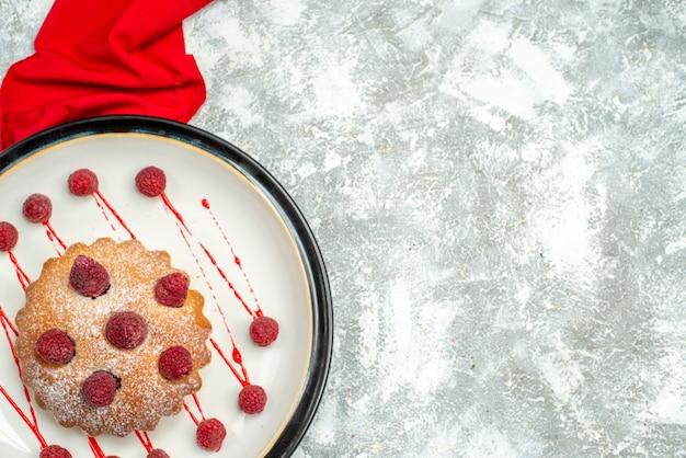 コピースペースのある灰色の表面に白い楕円形のプレートの赤いショールの上面図ベリーケーキ