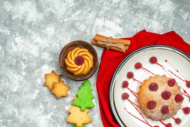 灰色の表面の空きスペースに白い楕円形のプレート赤いショールクリスマスツリークッキーの上面図ベリーケーキ