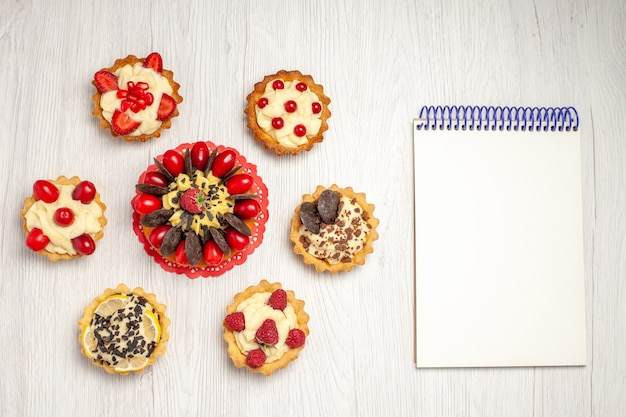 Top view berry cake on the red oval lace doily tarts and a notebook on the white wooden ground