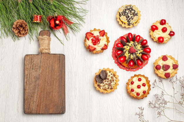Top view berry cake rounded with tarts pine tree leaves with christmas toys and a chopping board on the white wooden ground