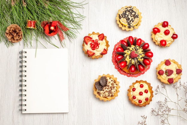 Top view berry cake rounded with tarts pine tree leaves with christmas toys and a notebook on the white wooden ground