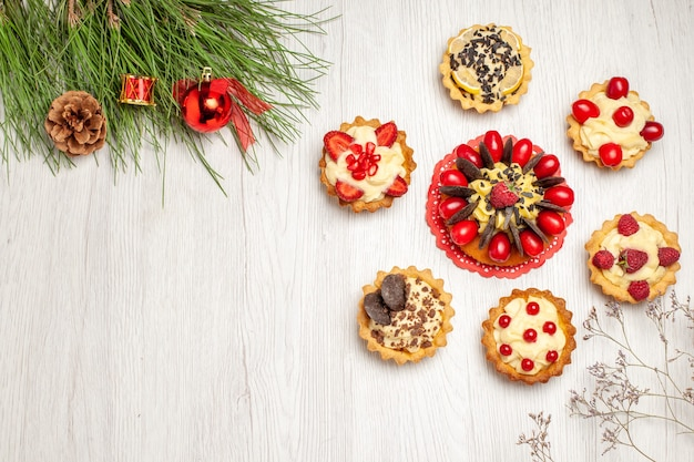 Top view berry cake rounded with tarts and pine tree leaves with christmas toys on the white wooden ground
