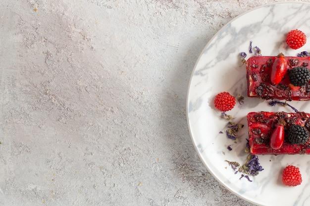 Вид сверху кусочками ягодного торта с красной сливочной глазурью и свежими ягодами на белой поверхности