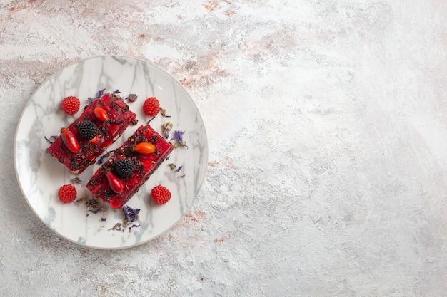 Fette di torta di frutti di bosco vista dall'alto con glassa cremosa rossa e frutti di bosco freschi su superficie bianca