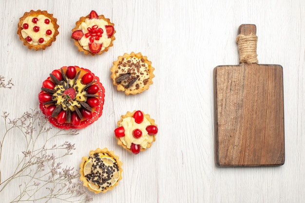 Top view berry cake surrounded berry and chocolate tarts at the left and a chopping board at the right side of the white wooden ground