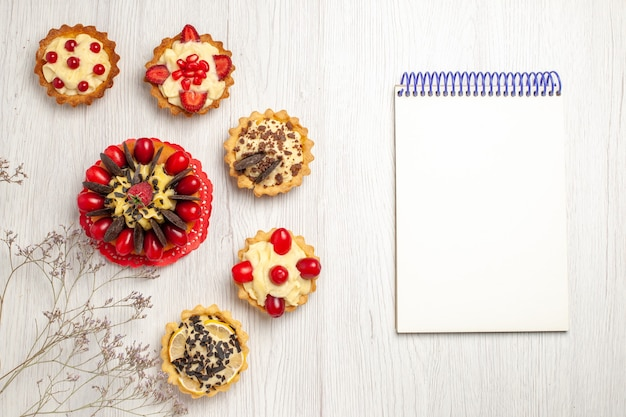 Top view berry cake surrounded berry and chocolate tarts at the left and a notebook at the right side of the white wooden ground