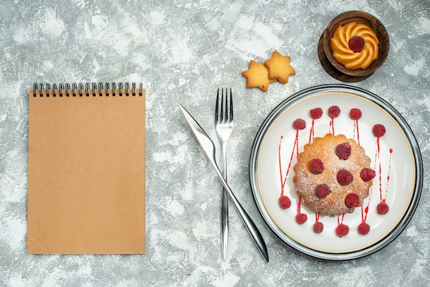 Top view berry cake on white oval plate biscuits in bowl fork and dinner knife notebook on grey surface