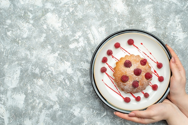 Top view berry cake on white oval plate in female hand on grey surface free place