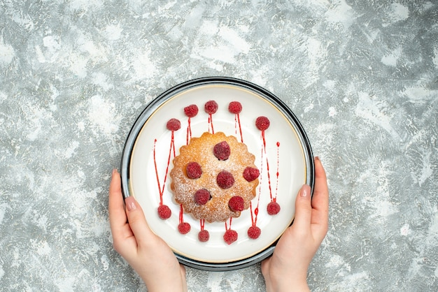 Top view berry cake on white oval plate in female hand on grey surface free space