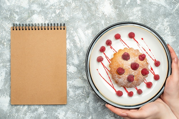 Top view berry cake on white oval plate in female hand notepad on grey surface