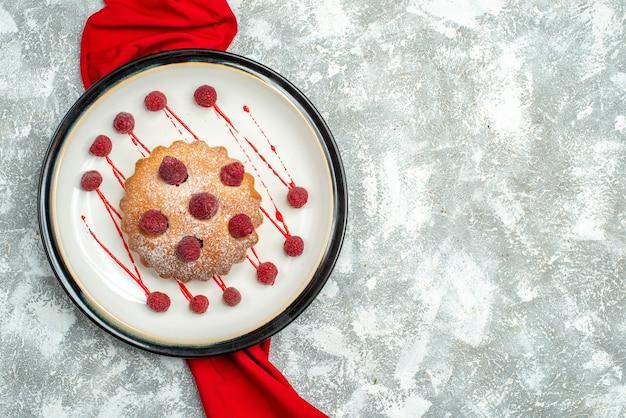 Torta di bacche vista dall'alto su scialle rosso piatto ovale bianco su spazio libero superficie grigia