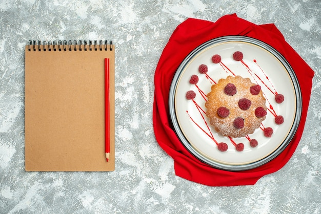 Top view berry cake on white oval plate red shawl red pencil on notebook on grey surface