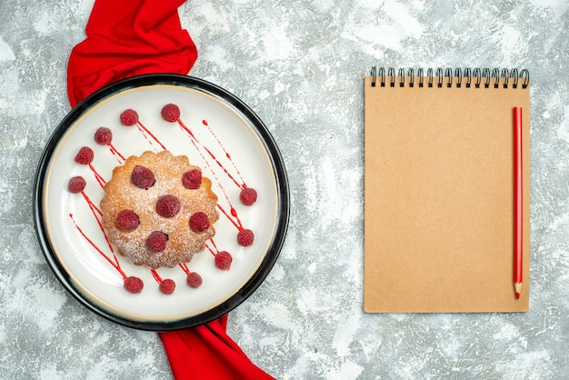 Top view berry cake on white oval plate red shawl red pencil on notepad on grey surface