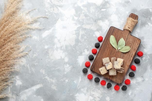 Vista dall'alto di confetture di frutti di bosco con cialde al cioccolato su luce, zucchero candito cialda dolce