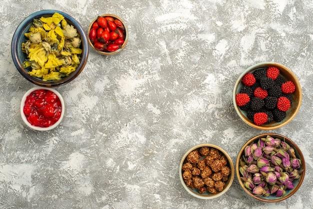 Vista dall'alto berry confitures con noci e fiori secchi su sfondo bianco confettura caramelle tè dolce
