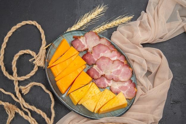 Vista dall'alto dei migliori snack deliziosi per il vino su un asciugamano e una corda su un tavolo scuro