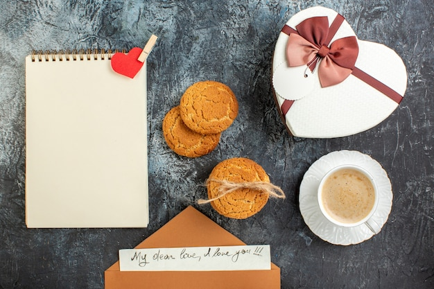 Top view of best surprise with beautiful gift boxes envelope with letter a cup of coffee cookies for beloved one on icy dark surface