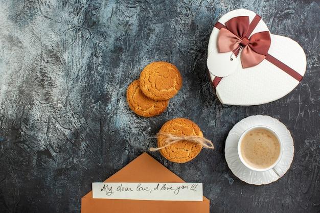 Vista dall'alto della migliore sorpresa con bellissime scatole regalo busta con lettera una tazza di biscotti al caffè per la persona amata sul lato sinistro su sfondo scuro ghiacciato