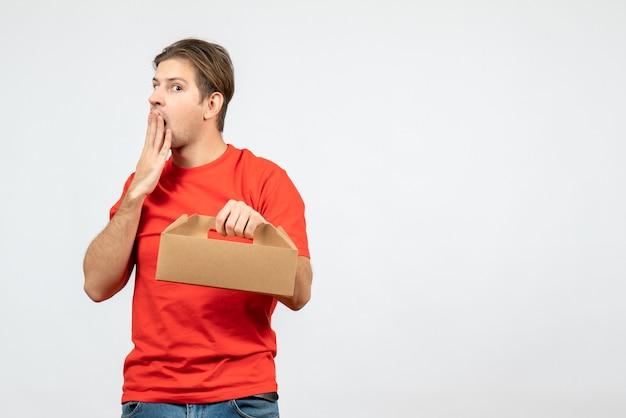 Vista dall'alto del giovane sconcertato ed emotivo in camicetta rossa che tiene scatola su sfondo bianco