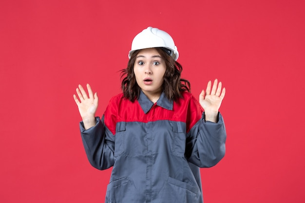 Top view of bewildered female builder in uniform with hard hat on isolated red background