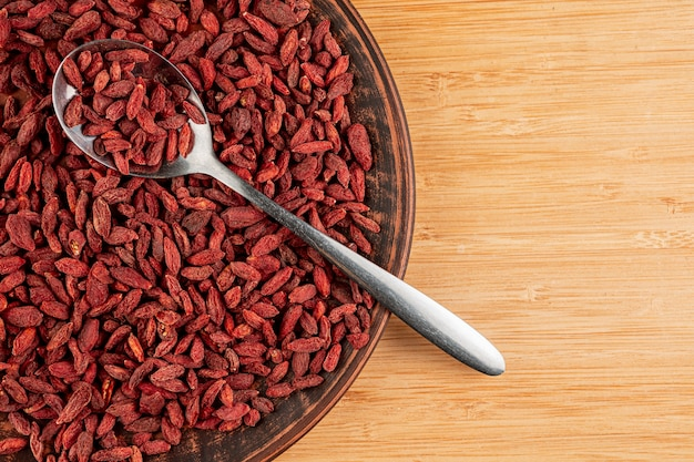 Top view big bowl with goji berries and wooden background