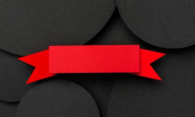 黒い紙とリボンの背景の上面の大きなドット