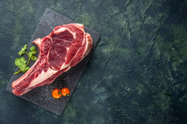 Vista dall'alto grande fetta di carne carne cruda su superficie scura