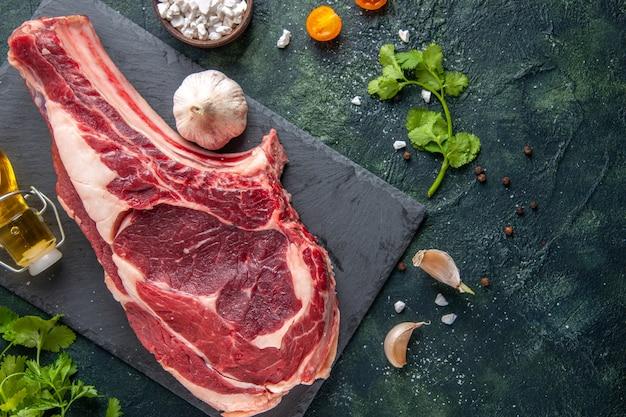 Вид сверху большой кусок мяса сырое мясо с зеленью на темной поверхности