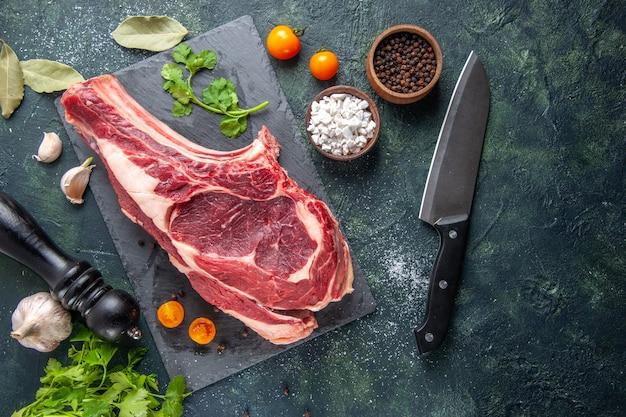 Вид сверху большой кусок мяса сырое мясо с перцем и зеленью на темной поверхности