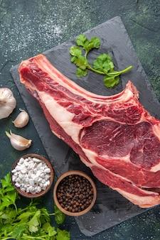 어두운 표면에 후추와 채소를 곁들인 상위 뷰 큰 고기 슬라이스 생고기