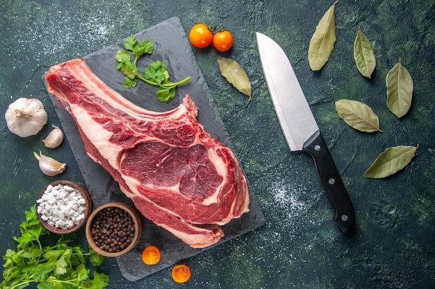 Vista dall'alto grande fetta di carne carne cruda con pepe e verdure su superficie scura