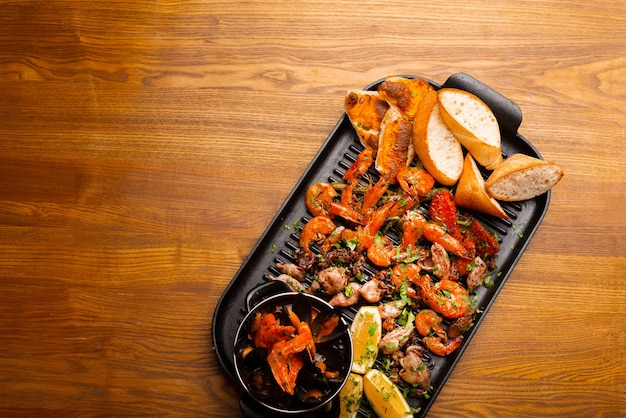 Top view big pan with grilled sea food, mussels shrimps and others