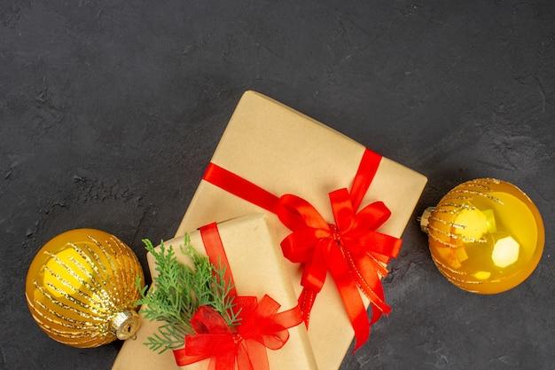 Vista dall'alto regali di natale grandi e piccoli in carta marrone legati con palline di nastro rosso su una superficie scura