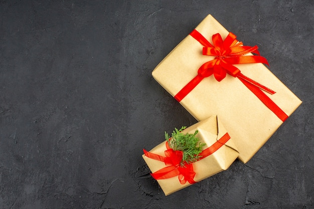 Vista dall'alto regali di natale grandi e piccoli in carta marrone legati con abete di rami di nastro rosso su sfondo scuro spazio libero