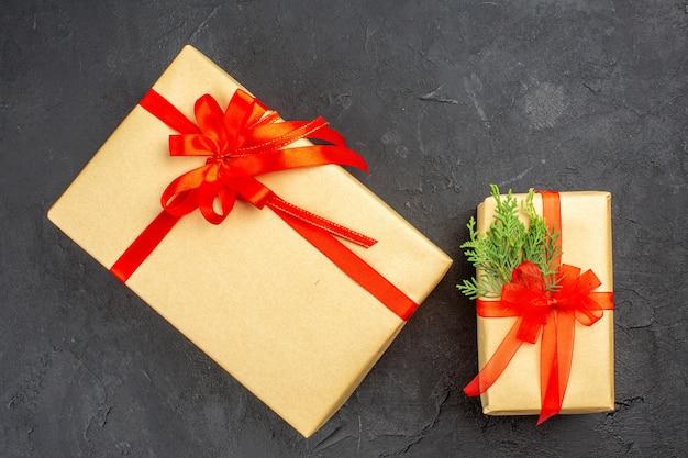 Vista dall'alto regali di natale grandi e piccoli in carta marrone legati con abete di ramo di nastro rosso su superficie scura