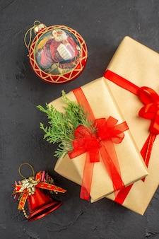 Vista dall'alto regali di natale grandi e piccoli in carta marrone legati con giocattoli di albero di natale di abete ramo di nastro rosso su sfondo scuro dark