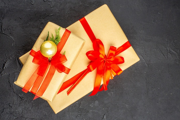 Top view big and small xmas gifts in brown paper tied with red ribbon on dark background with free space