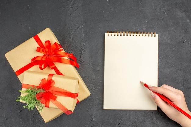 Vista dall'alto regali di natale grandi e piccoli in carta marrone legati con una matita per quaderni a nastro rosso in mano femminile su superficie scura