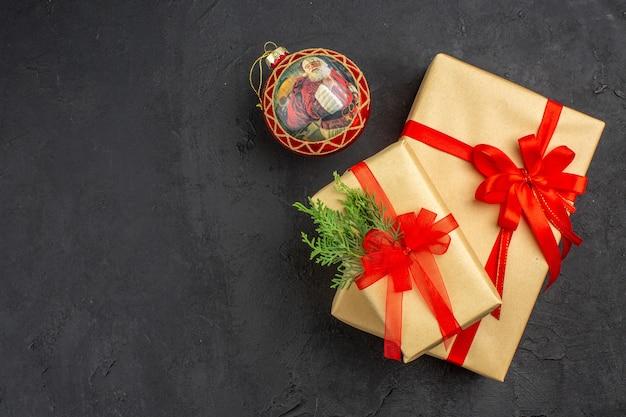 Vista dall'alto regali di natale grandi e piccoli in carta marrone legati con una palla di natale con nastro rosso su sfondo scuro posto libero