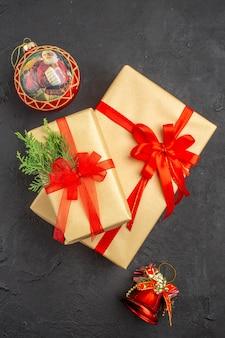 Vista dall'alto regali di natale grandi e piccoli in carta marrone legati con giocattoli di albero di natale con nastro rosso su sfondo scuro