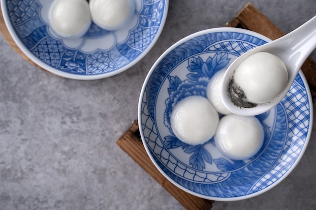 Top view of big tangyuan yuanxiao (glutinous rice dumpling balls) for lunar new year festival food, words on the golden coin means the dynasty name it made.