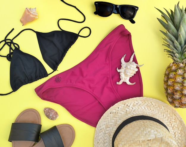 Top view on bikini and beach accessories with pineapples and seashells on yellow background