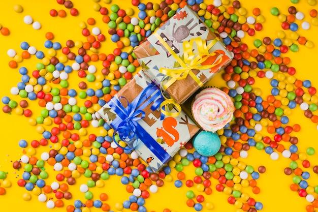 Elementi di compleanno di vista superiore circondati da bonbon colorati