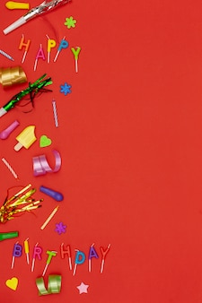 Top view birthday ornaments on red background