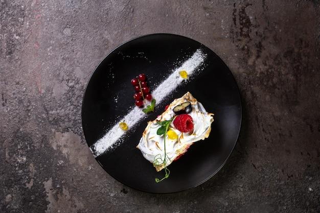 Бисквитный рулет с ягодами на стильной черной тарелке вид сверху