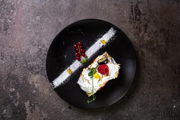 Top view biscuit roll with berries on a stylish black plate
